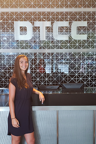 Zenya Koprowski in front of the DTCC sign at her internship.