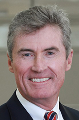 Sean Hanlon, in a dark suit, smiling against a gray backdrop.