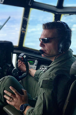 Mark Roberson sitting in the cockpit of a C-130.