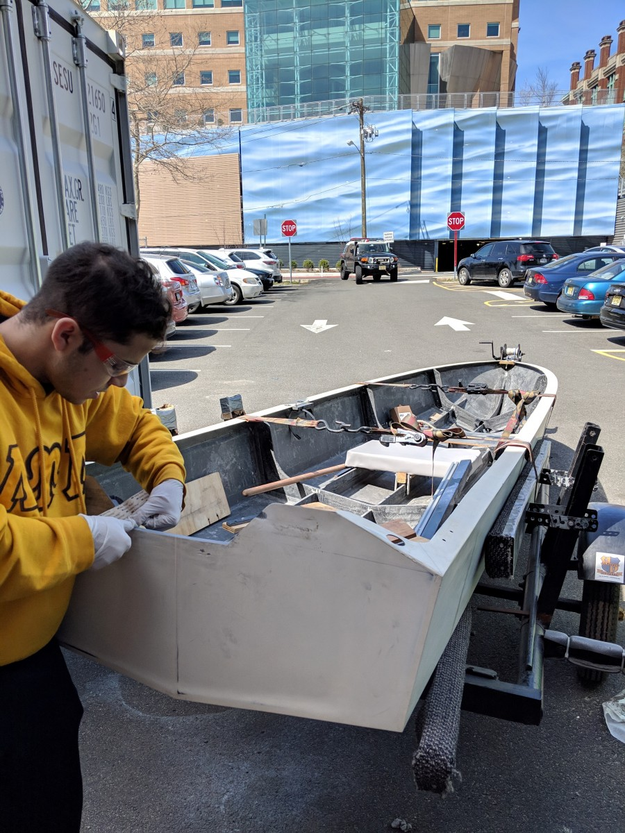 Student cutting the boat's transom to accommodate a new outboard unit