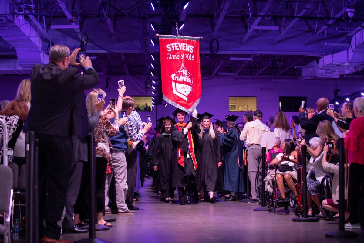 Students enter the arena led by the Class of 2018 banner