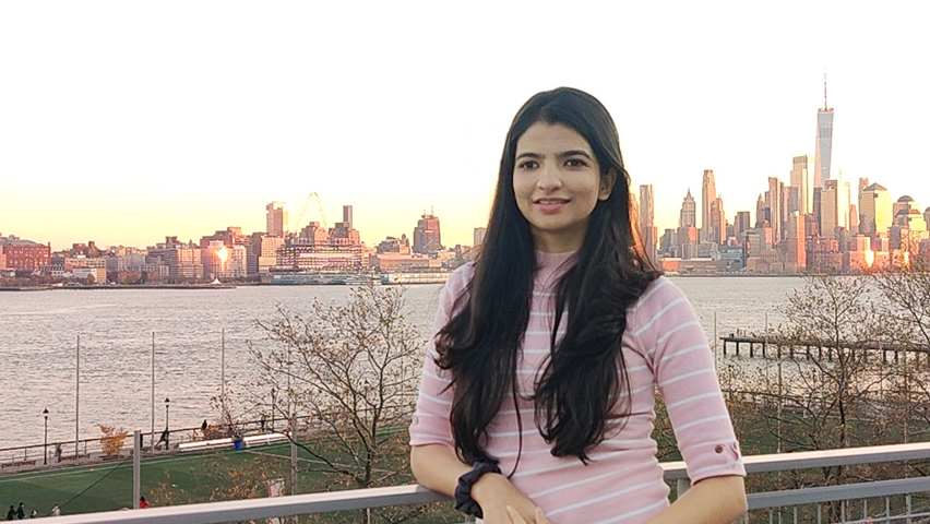 Aayushi Gandhi with the lower Manhattan skyline in the background.