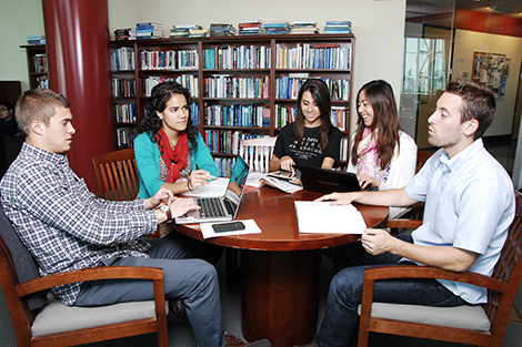 A group of five students working on a project around a table in a study space in the Babbio Center.