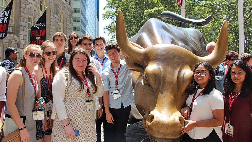 A group of students surrounding the bronze Charging Bull statue in New York City.