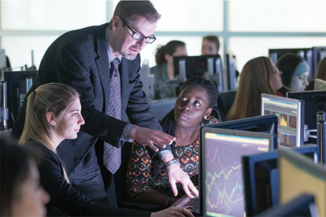 Two female students listen as a professor goes through Bloomberg data with them in a lab.