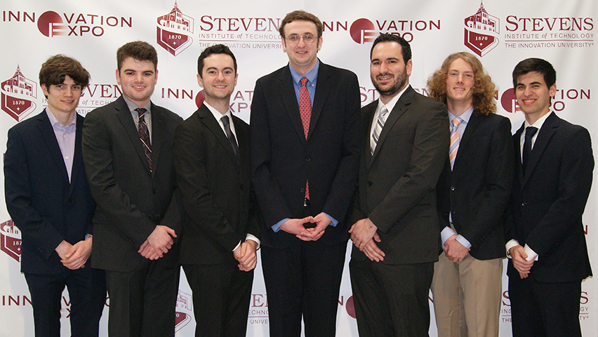 The seven students behind Coin Complex in front of the Stevens logo.