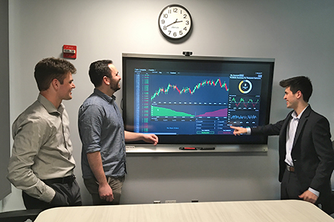 The three business students on Coin Complex walk through the exchange's interface in a high-tech lab.