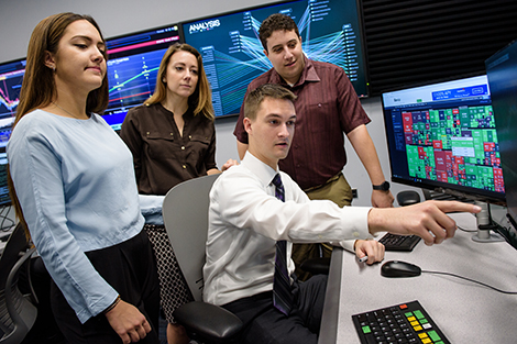 Two male and two female students work collaboratively with data visualization technology in a Stevens lab.