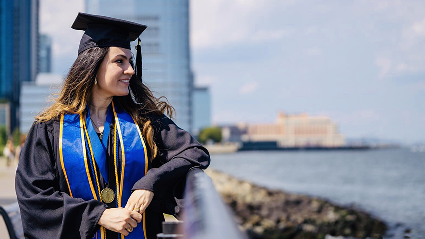 Fatine Zaaj, in cap and gown, on the Hudson River in Jersey City.