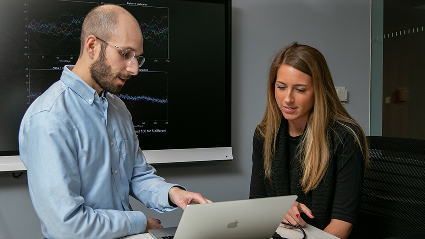A male professor and female student look at some data on a laptop screen.