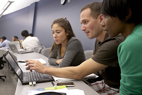 A group of three Stevens students reviews some findings as they prepare a presentation in their management class.