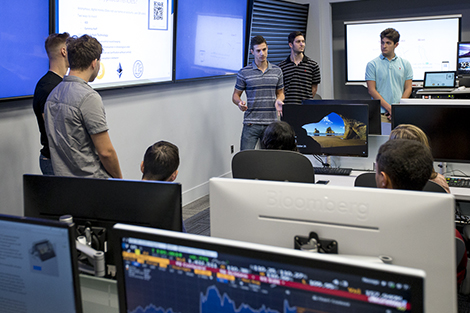 A group of freshmen present a project on cryptocurrency in the Hanlon Lab at Stevens. Bloomberg terminals are visible in the foreground.