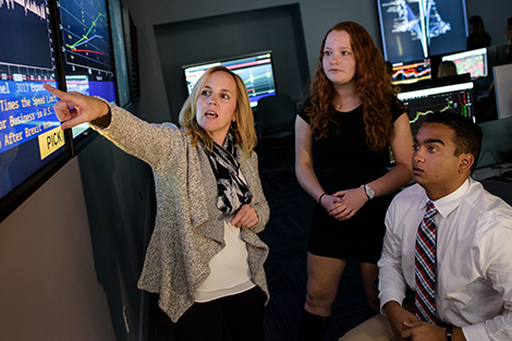 A female professor works with two students in examining high-frequency data on a smartboard in the Hanlon Lab.