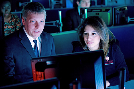 The glow of a Bloomberg terminal lights up a female student's face as Dr. Bozdog provides some coaching on the platform.