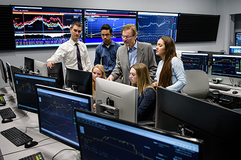 Five students gather around Dr. Calhoun as he points out market data on a Bloomberg terminal in Hanlon 2.