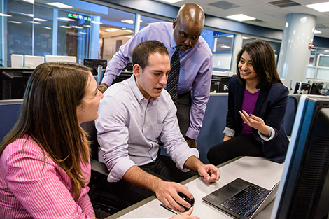 A group of male and female graduate business students collaborate around a Bloomberg terminal in the Hanlon Lab.
