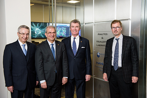 The leaders of the Hanlon Financial Systems Center pose in front of the glass wall entrance to the lab. In the background are screens showing financial data.
