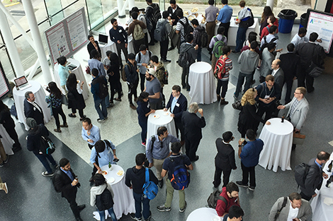 An overhead photo of conference attendees mingling with students and faculty as they look at research posters.