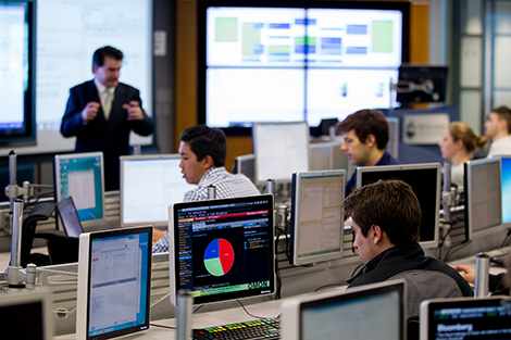 A male student works at a Bloomberg terminal as his professor leads a class in the Hanlon lab.