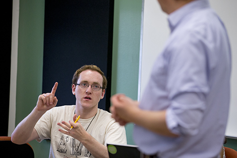 A student answers questions from a professor during a management class.