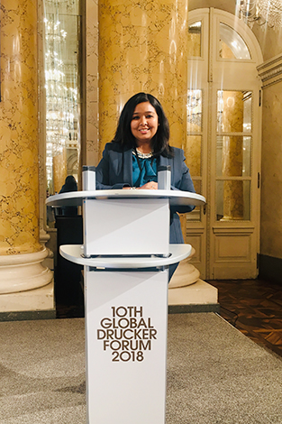 Kanika Ghocha in front of the podium at the Drucker Forum in Vienna.