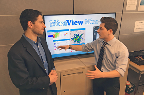 Two students present their business concept in a conference room.