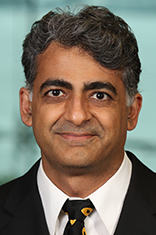 Headshot of Dr. Murad Mithani in a black jacket and dark tie with the New York City skyline in the background.