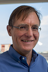Headshot of Dr. Nickerson in a blue shirt with the Hoboken skyline in the background.