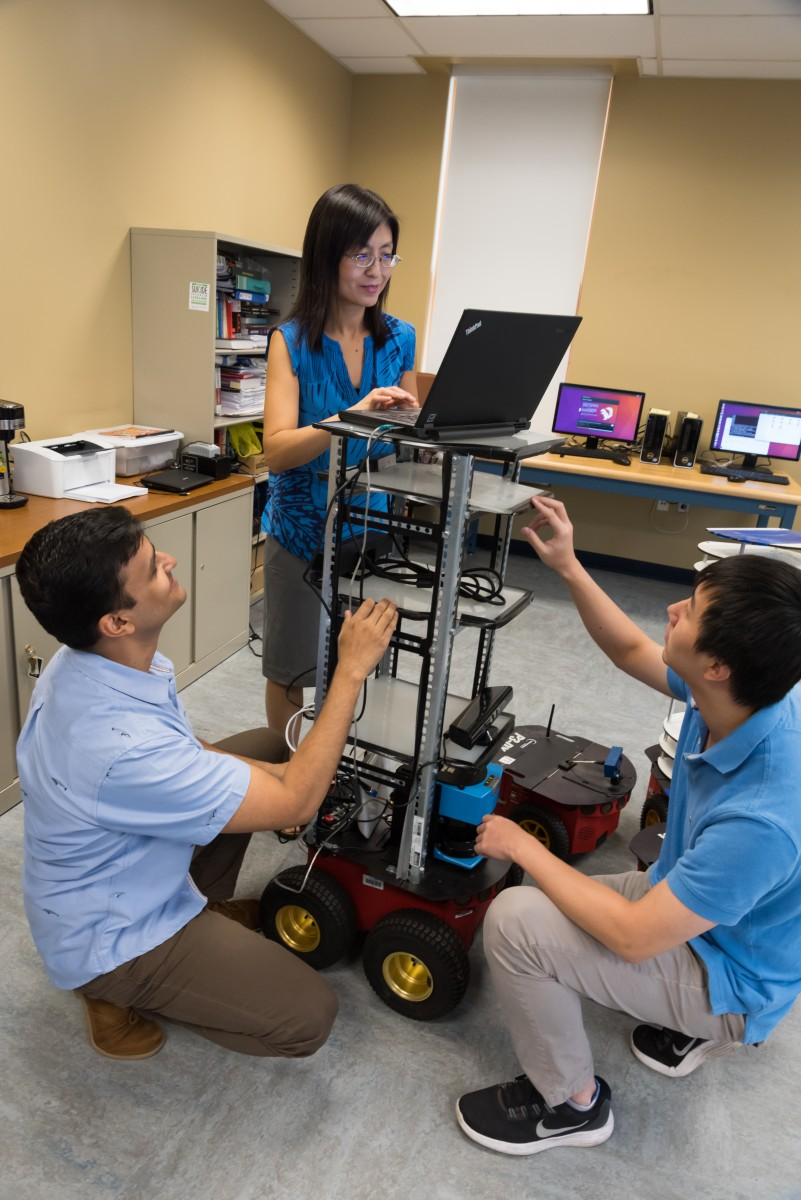 Guo and students Muhammad Fahad and Chao Jiang in the Robotics and Automation Laboratory