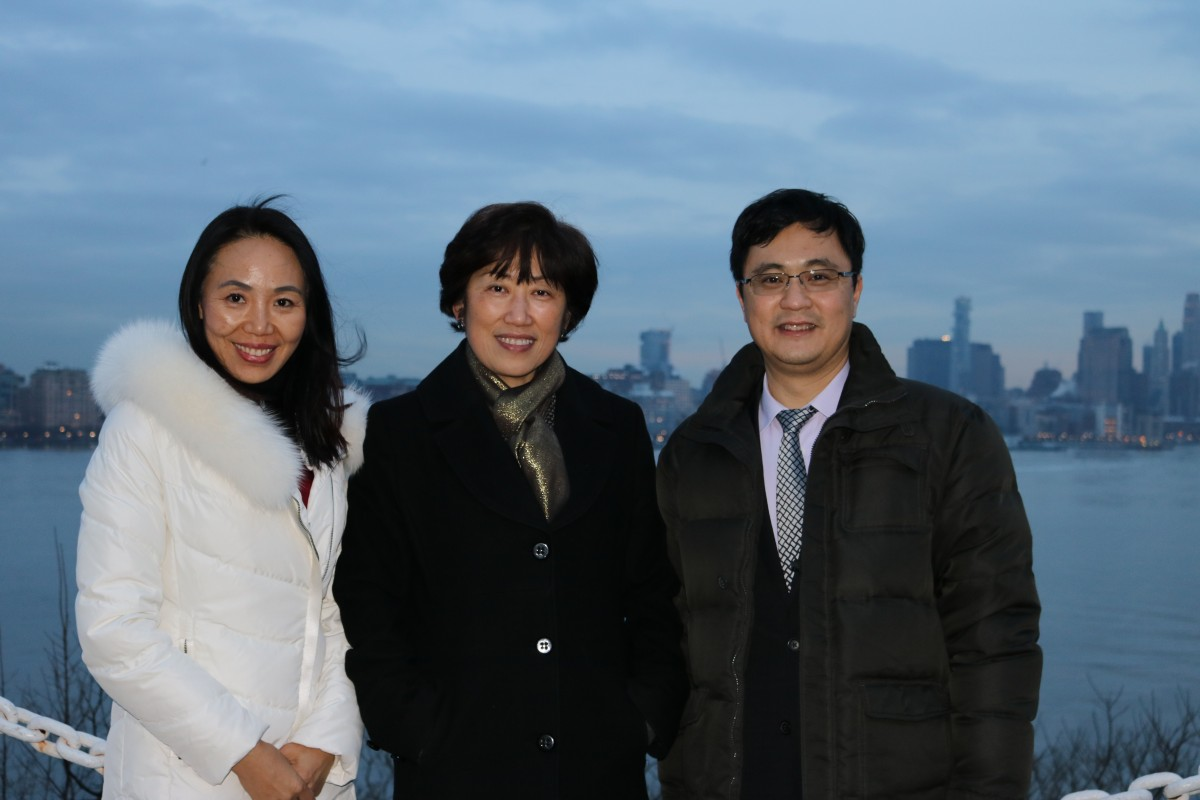 Annie Song, Dean Zu and Lin Zhang on campus, with downtown Manhattan in the background.