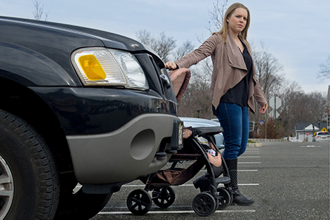 A woman walks alongside her stroller from behind a parked SUV.