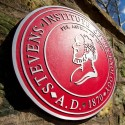 University seal on a brick wall with a blue cloudy sky in the background.