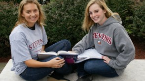 Students studying outside smiling at camera