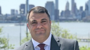 Chris Colla in a gray suit and red tie, with New York City in the background.