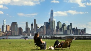 Students sitting on the lawn at Stevens with the Freedom Tower and downtown NYC in the background