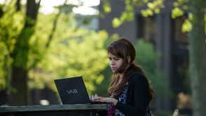 Student working on laptop at a table on campus