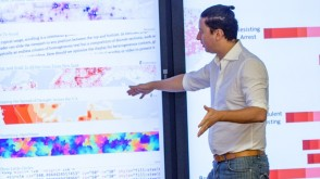 Faculty member using visual data on large screens to teach