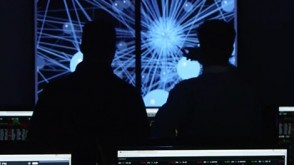 Two male researchers point to data on a screen in a darkened lab.