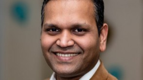 Sanjay in a tan jacket and dress shirt before a screen containing data.