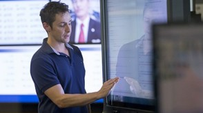 Dr. Ted Lappas, in a blue polo, gestures on a touchscreen in the lab. Other screens showing financial news are running in the backdrop.
