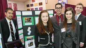 Five undergraduate students pose near signage showcasing their research project at the Innovation Expo.