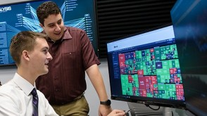 Two students point out some data on a Bloomber terminal in the lab.