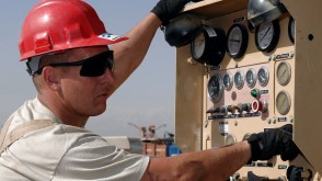 Man in a hard hat at a control switch