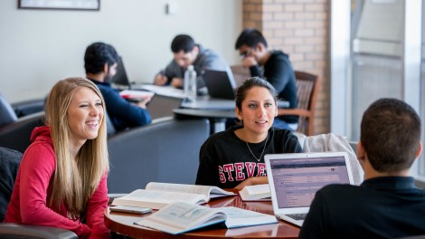 Students smiling while working at a table