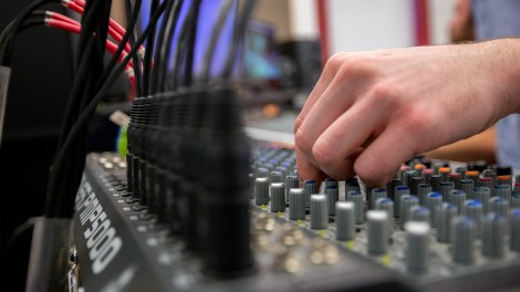 hand touching controls on mixing board