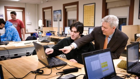 Professor and student pointing to something on a laptop screen