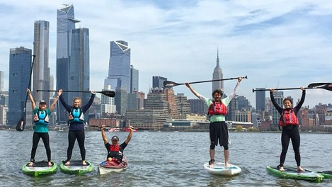 A group of Stevens students on paddleboards in the Hudson River. The New York City skyline is in the background.