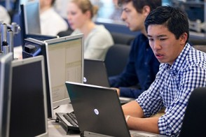 A student uses his laptop to take notes as he watches market data on a Bloomberg terminal in the lab.