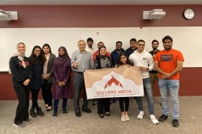 Group of students with Stevens MECA banner