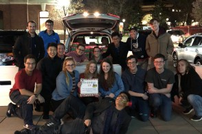 Group of students in front of a car with presents in the trunk